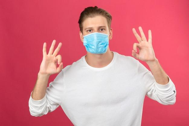 孤立したピンクの背景にカメラを見て指と手でokの標識を示す医療用防護マスクの若い男