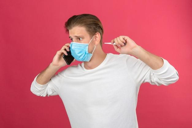 孤立したピンクの背景にパニックでスマートフォンで話す医療用防護マスクの若い男