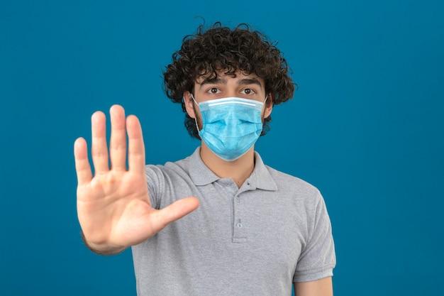 격리 된 파란색 배경 위에 심각하고 자신감이 표현 방어 제스처와 정지 신호를 하 고 손바닥으로 서 의료 보호 마스크에서 젊은 남자