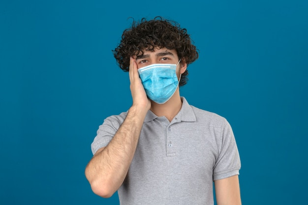孤立した青い背景に不幸な顔で立っている頭痛を持っている病気を探して頭に触れる医療用防護マスクの若い男