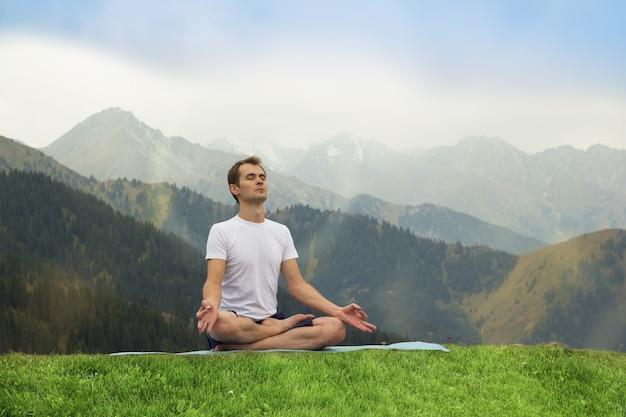 瞑想中の若い男山での屋外ヨガ