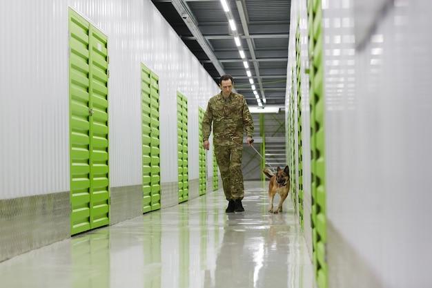Молодой человек в военной форме идет по коридору с собакой, чтобы проверить склад