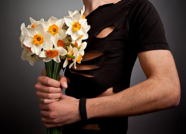 水仙の花の花束を保持しているモダンな黒い服を着た若い男