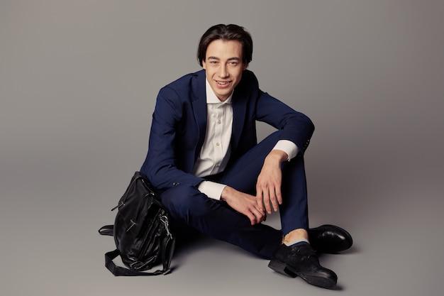검은 비즈니스 가방 회색 벽 위에 앉아 해군 소송에서 젊은 남자