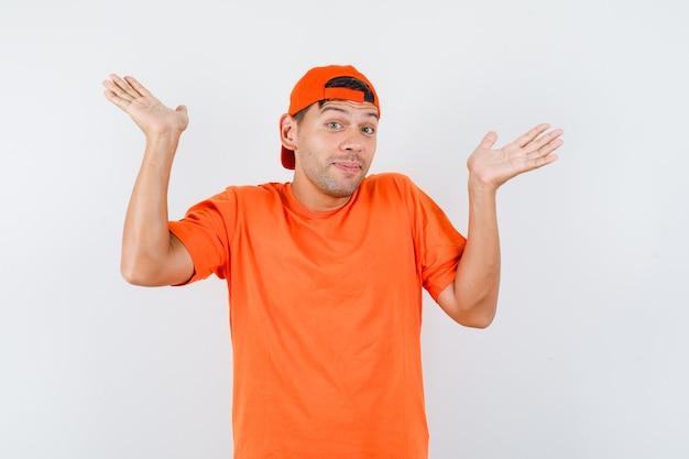 Молодой человек в оранжевой футболке и кепке беспомощно поднимает руки и выглядит мило