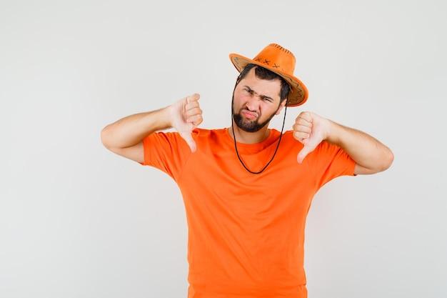 Молодой человек в оранжевой футболке, шляпе показывает двойные пальцы вниз и недоволен, вид спереди.