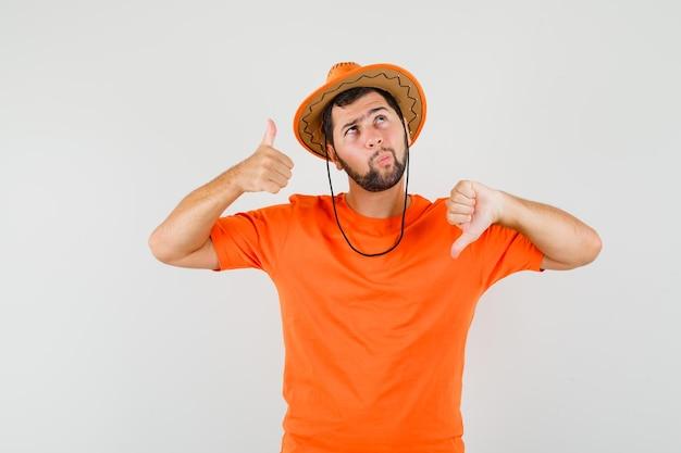 Молодой человек в оранжевой футболке, шляпе показывает большие пальцы руки вверх и вниз и нерешительно смотрит, вид спереди.