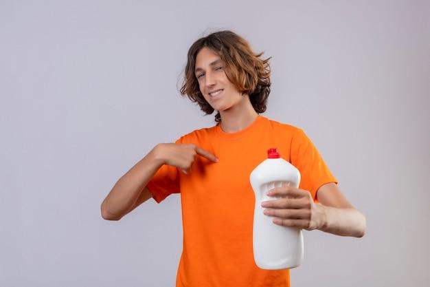 Молодой человек в оранжевой футболке держит бутылку чистящих средств, глядя в камеру, весело улыбаясь, указывая на себя с уверенным взглядом, стоя на белом фоне