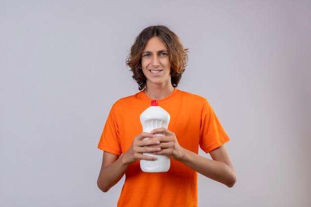 Молодой человек в оранжевой футболке держит бутылку чистящих средств, выглядит смущенным и обеспокоенным, стоя на белом фоне