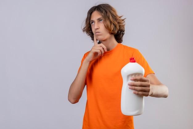 Молодой человек в оранжевой футболке держит бутылку чистящих средств, глядя вверх с пальцем на подбородке, думая, стоя на белом фоне