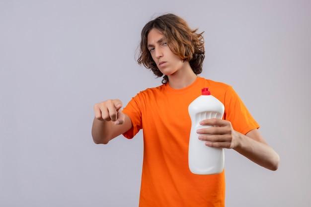 Молодой человек в оранжевой футболке держит бутылку чистящих средств, указывая на камеру, недоволен хмурым лицом, стоящим на белом фоне