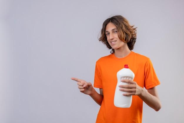 Молодой человек в оранжевой футболке держит бутылку чистящих средств, указывая в сторону, улыбаясь, уверенно глядя в камеру, стоящую на белом фоне