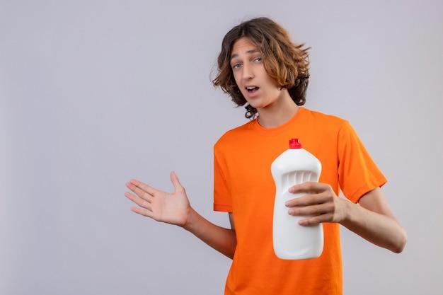 Молодой человек в оранжевой футболке держит бутылку чистящих средств, стоя с поднятой рукой, смущенный на белом фоне