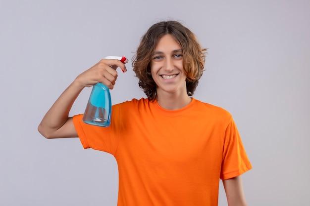 Молодой человек в оранжевой футболке держит чистящий спрей, глядя в камеру, весело улыбаясь, стоя на белом фоне