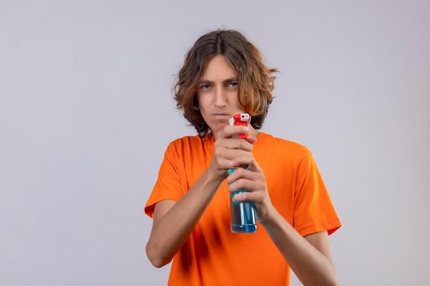 白い背景の上に立っている深刻な顔で脅迫しているカメラにクリーニングスプレー表示を保持しているオレンジ色のtシャツの若い男
