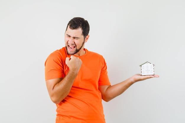 Молодой человек в оранжевой футболке держит модель дома с жестом победителя и выглядит удачливым, вид спереди.