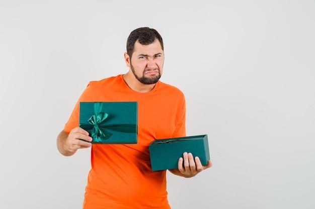 オレンジ色のtシャツを着た若い男がプレゼントボックスを開いて、不機嫌そうに見える、正面図。
