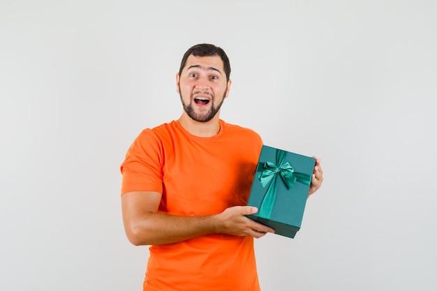 プレゼントボックスを持って嬉しそうに見えるオレンジ色のtシャツの若い男、正面図。