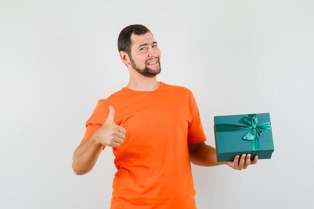 オレンジ色のtシャツを着た若い男は、親指を上に向けてプレゼントボックスを保持し、陽気に見える、正面図。