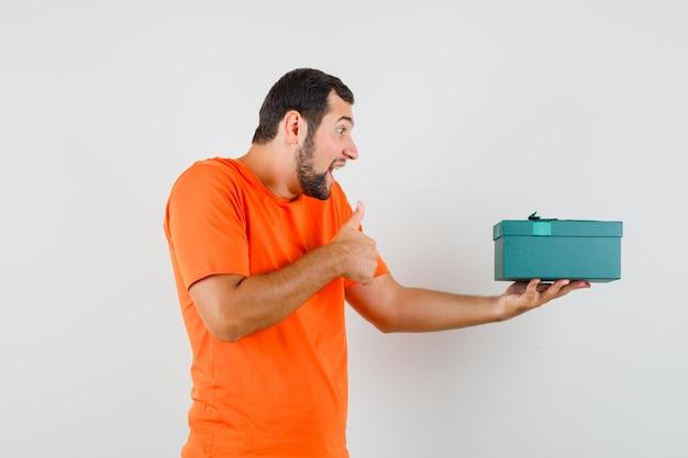 親指を上にして現在のボックスを保持し、幸せそうに見えるオレンジ色のtシャツの若い男、正面図。