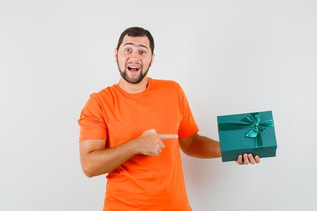 オレンジ色のtシャツを着た若い男が現在のボックスを指して、嬉しそうに見える、正面図。