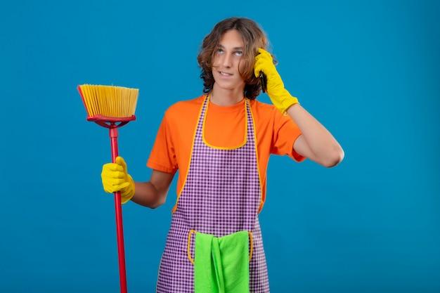 青い背景の上に立っている笑顔の携帯電話で話しているモップを保持しているエプロンとゴム手袋を身に着けているオレンジ色のtシャツの若い男