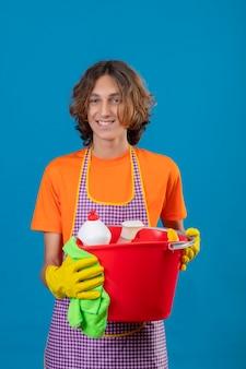 青い背景に肯定的で幸せな立っている笑顔のカメラを見てクリーニングツールでバケツを保持しているエプロンゴム手袋を身に着けているオレンジ色のtシャツの若い男