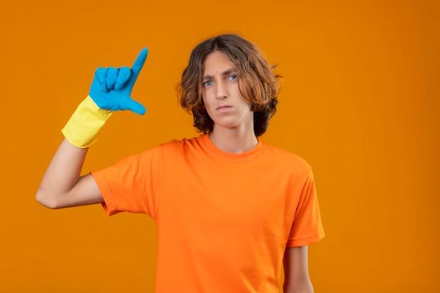 黄色の背景の上に立っている深刻な顔測定シンボルと小さなサイズのサインを示す手で身振りで示すゴム手袋を身に着けているオレンジ色のtシャツの若い男