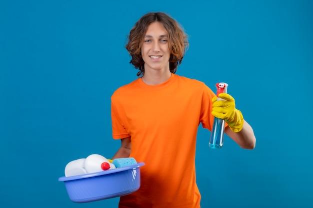 オレンジ色のtシャツを着たゴム製の手袋を身に着けている洗面器を保持しているゴム手袋を着用し、青い背景の上に立っている顔に笑顔でカメラを見てスプレーを洗浄