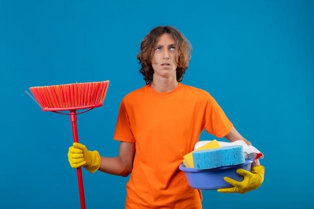 オレンジ色のtシャツを着てゴム手袋を着用して洗面器のクリーニングツールとモップ青い背景の上に混乱して不安な立っているを探して身に着けている若い男