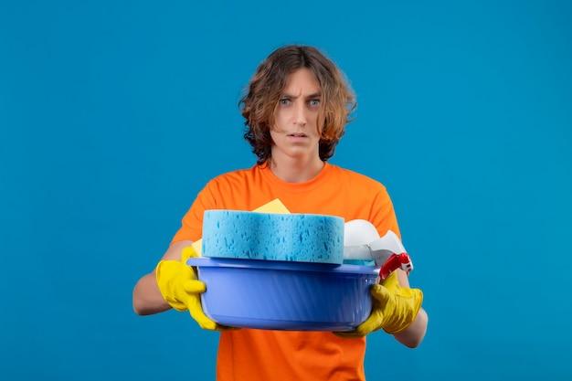青い背景の上に立っている顔に怒りの表情で不機嫌なカメラを見てクリーニングツールで盆地を保持しているゴム手袋を着用してオレンジ色のtシャツの若い男