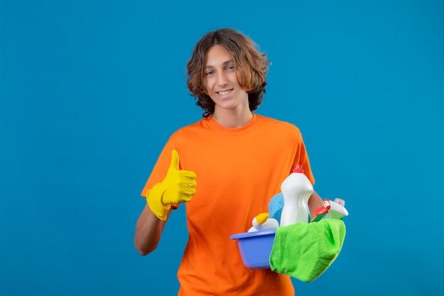 青色の背景の上に立って親指を元気に見せて笑顔のカメラを見てクリーニングツールで盆地を保持しているゴム手袋を着用してオレンジ色のtシャツの若い男