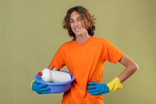 緑の背景の上に肯定的で幸せな立っている笑顔カメラを見てクリーニングツールで洗面器を保持しているゴム手袋を着用してオレンジ色のtシャツの若い男