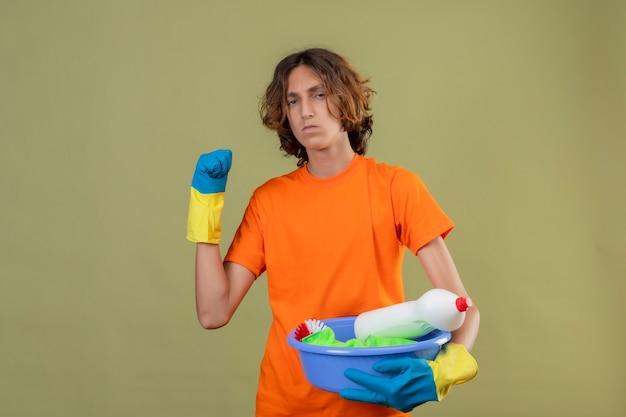 緑の背景の上に立って顔をしかめ顔をしかめて拳を脅かす拳を上げるクリーニングツールで盆地を保持しているゴム手袋を着用してオレンジ色のtシャツの若い男