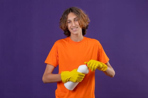 紫色の背景の上に元気に立ってカメラ笑顔を見てクリーニング用品のボトルを保持しているゴム手袋を着用してオレンジ色のtシャツの若い男