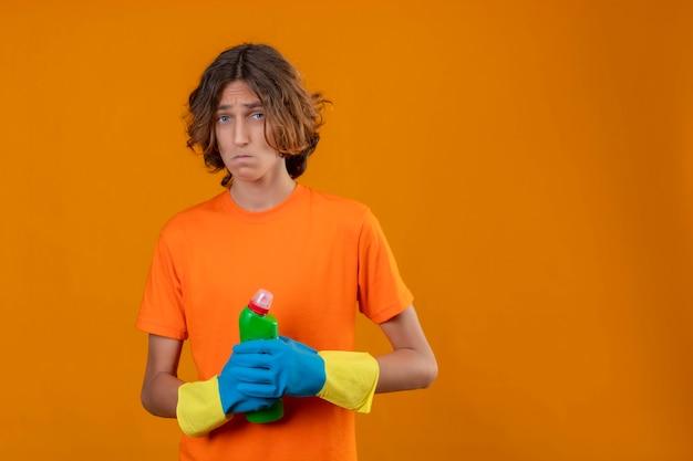 オレンジ色のtシャツの若い男が黄色の背景に混乱して非常に心配して立っている探しているクリーニング用品のボトルを保持しているゴム手袋を着用