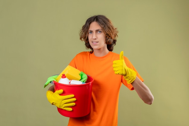 緑の背景の上に立って親指を元気に見せて笑顔のカメラを見てクリーニングツールでバケツを保持しているゴム手袋を着用してオレンジ色のtシャツの若い男