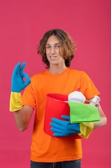 Молодой человек в оранжевой футболке в резиновых перчатках держит ведро с инструментами для уборки, глядя в камеру, уверенно улыбается, делает хорошо, знак стоит на розовом фоне