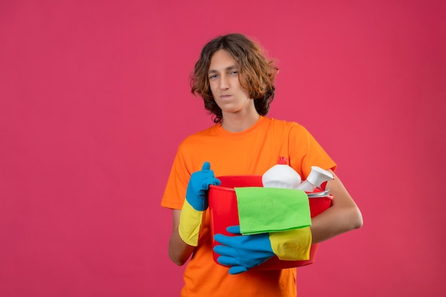 Молодой человек в оранжевой футболке в резиновых перчатках держит ведро с чистящими средствами и смотрит в камеру со скептическим выражением лица, стоя на розовом фоне