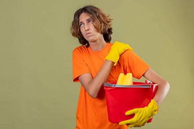 緑の背景の上に立って痛みを持っている肩に触れて体調不良を探してクリーニングツールでバケツを保持しているゴム手袋を着用してオレンジ色のtシャツの若い男