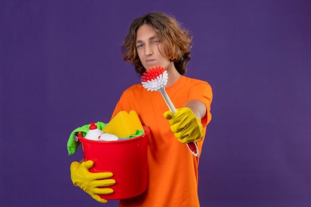 Молодой человек в оранжевой футболке в резиновых перчатках держит ведро с инструментами для уборки, показывая щетку в камеру, уверенно смотрит в камеру, стоя на фиолетовом фоне
