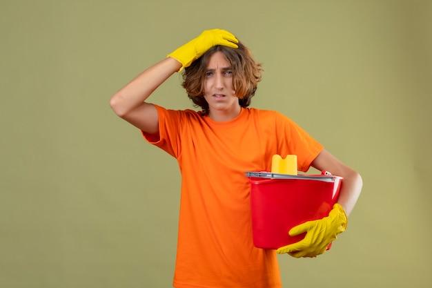 緑の背景で混乱して探しているミスの頭の上に手で立っているツールをクリーニングでバケツを保持しているゴム手袋を着用してオレンジ色のtシャツの若い男