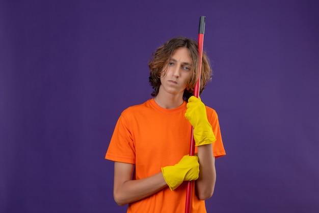 紫色の背景の上に立っている顔に悲しそうな表情でカメラを見てモップを保持しているゴム手袋を着用してオレンジ色のtシャツの若い男