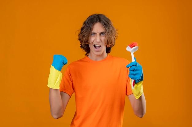 Молодой человек в оранжевой футболке в резиновых перчатках держит щетку, сжимая кулак, радуясь своему успеху и победе, и счастлив, стоя на желтом фоне