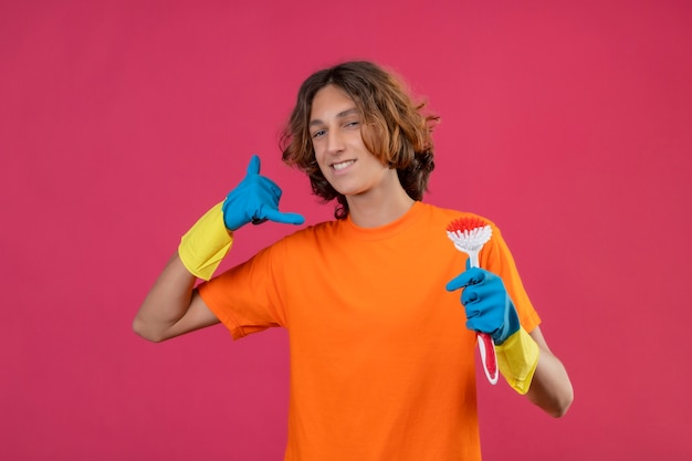 ピンクの背景の上に立って私をジェスチャーと呼ぶ自信を持って笑顔でカメラを見てスクラブブラシを保持しているゴム手袋を着用してオレンジ色のtシャツの若い男