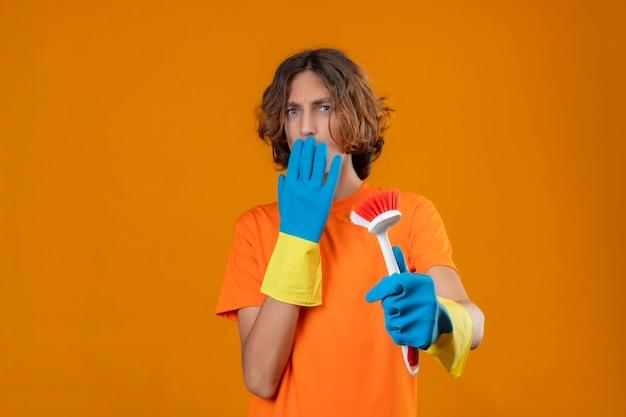 黄色の背景の上に立って手でショックを受けた覆い口を探してスクラブブラシを保持しているゴム手袋を着用してオレンジ色のtシャツの若い男