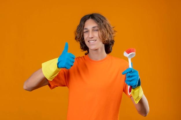 Молодой человек в оранжевой футболке в резиновых перчатках держит щетку для чистки, улыбаясь счастливым лицом, показывая пальцы вверх, стоя на желтом фоне