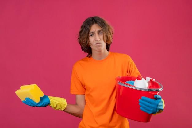 スポンジとバケツを保持しているゴム手袋をはめたオレンジ色のtシャツの若い男