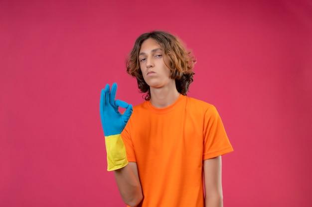 Молодой человек в оранжевой футболке в резиновых перчатках выглядит уверенно, делает хорошо, знак стоит на розовом фоне