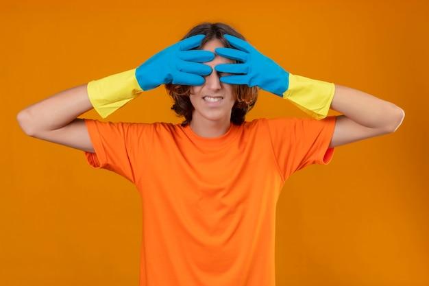 黄色の背景の上に立って驚きを待っている手で彼の目を覆っている笑顔のゴム手袋を着用してオレンジ色のtシャツの若い男